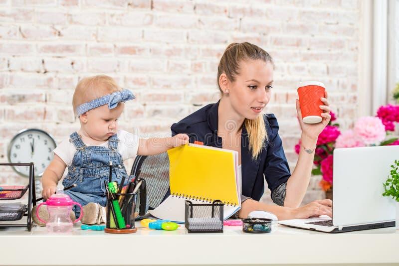 Femme de mère de femme d'affaires avec une fille travaillant à l'ordinateur portable photo stock
