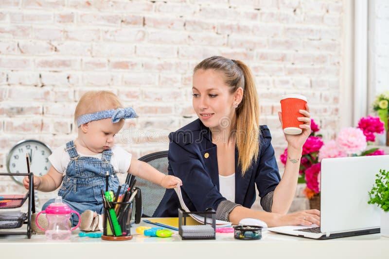 Femme de mère de femme d'affaires avec une fille travaillant à l'ordinateur portable photographie stock