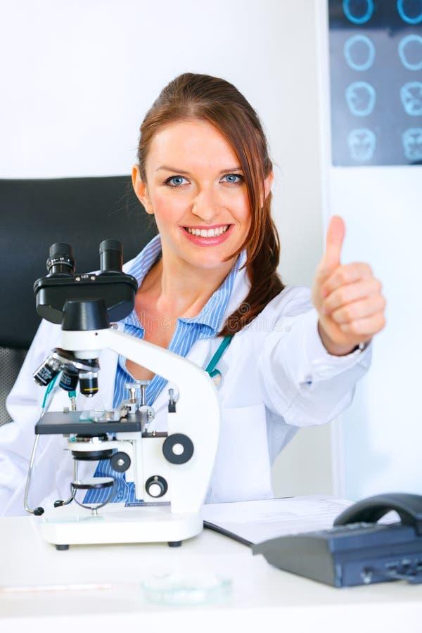 Femme de médecin à l'aide du microscope dans le laboratoire photos stock