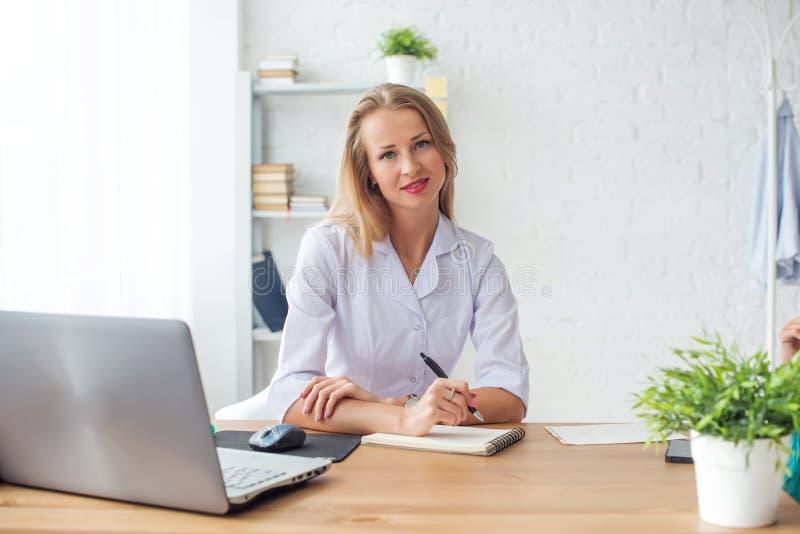 Femme de médecin s'asseyant au bureau dans médical image stock