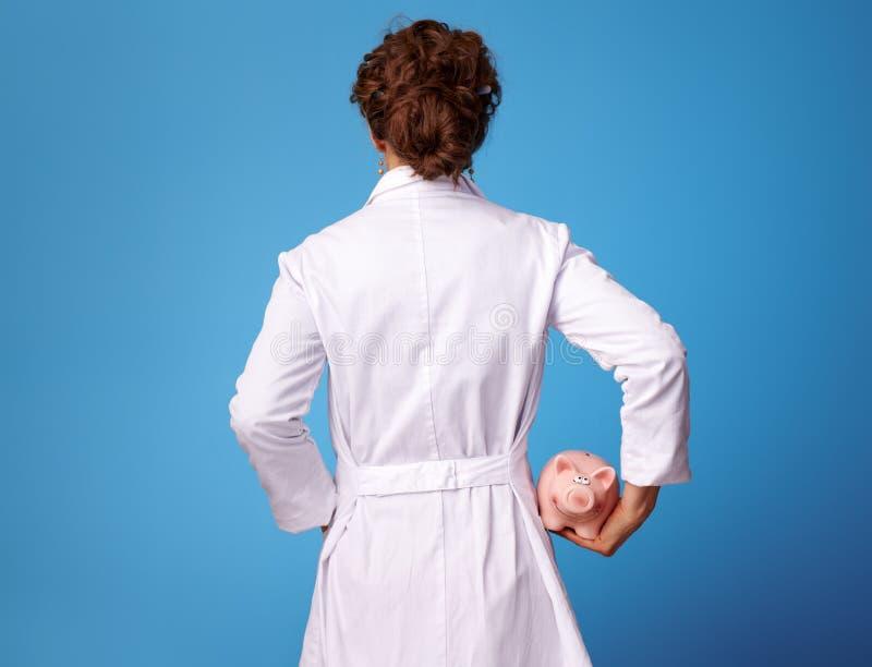 Femme de médecin tenant la tirelire sur le bleu photos stock