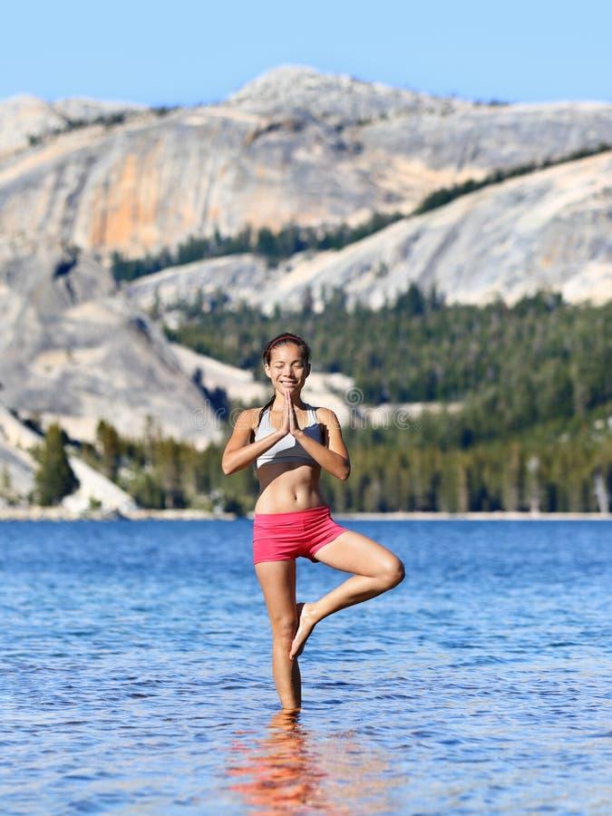 Femme de méditation de yoga méditant dans le lac de nature photographie stock libre de droits
