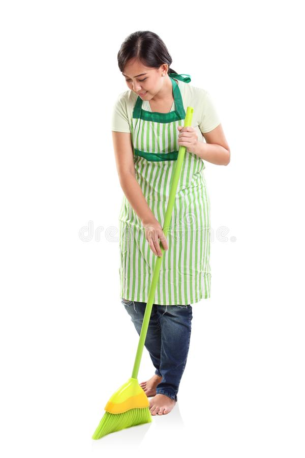 Femme de ménage balayant le plancher, portrait de studio images stock