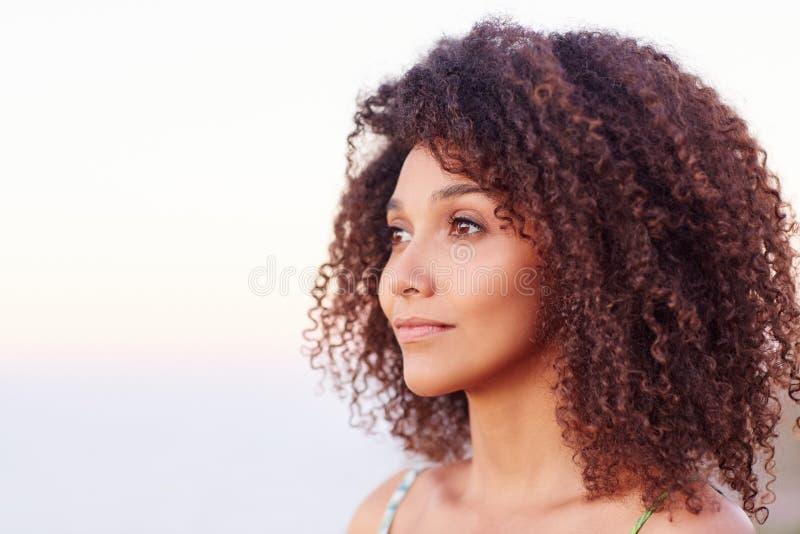 Femme de métis avec les cheveux Afro regardant loin serein dehors photos stock