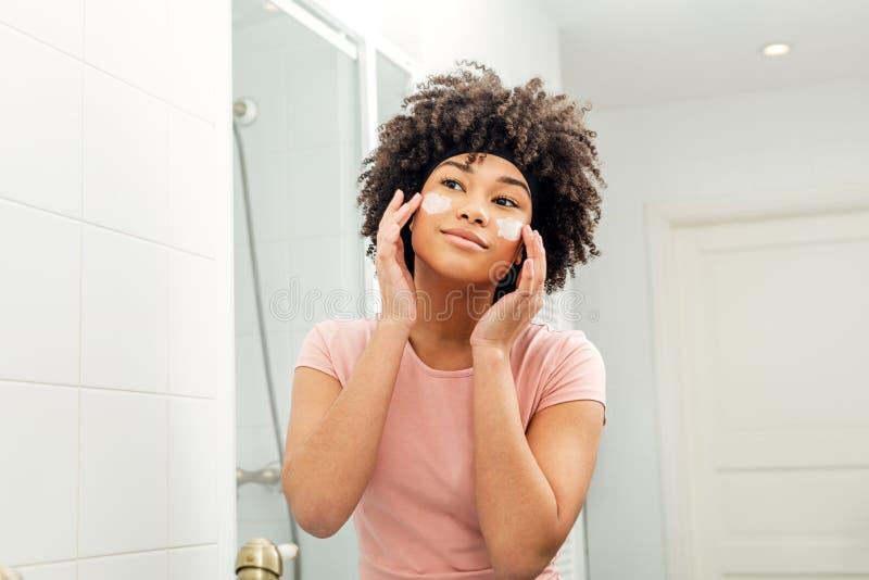 Femme de métis dans la salle de bains regardant dans le miroir photo stock