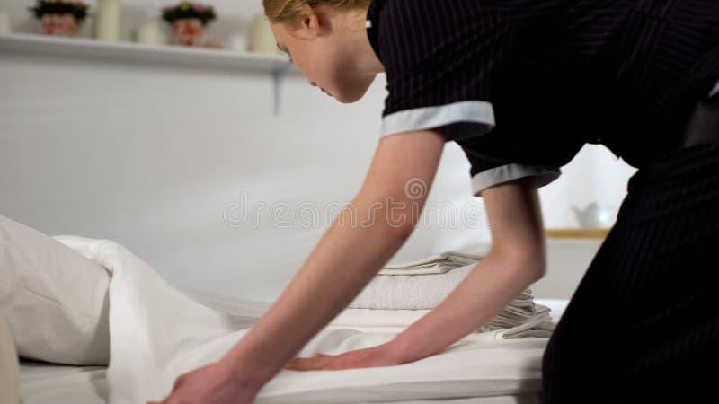 Femme de m?nage faisant le lit, pr?parant la chambre d'h?tel pour la nouvelle arriv?e d'invit?s, service images stock