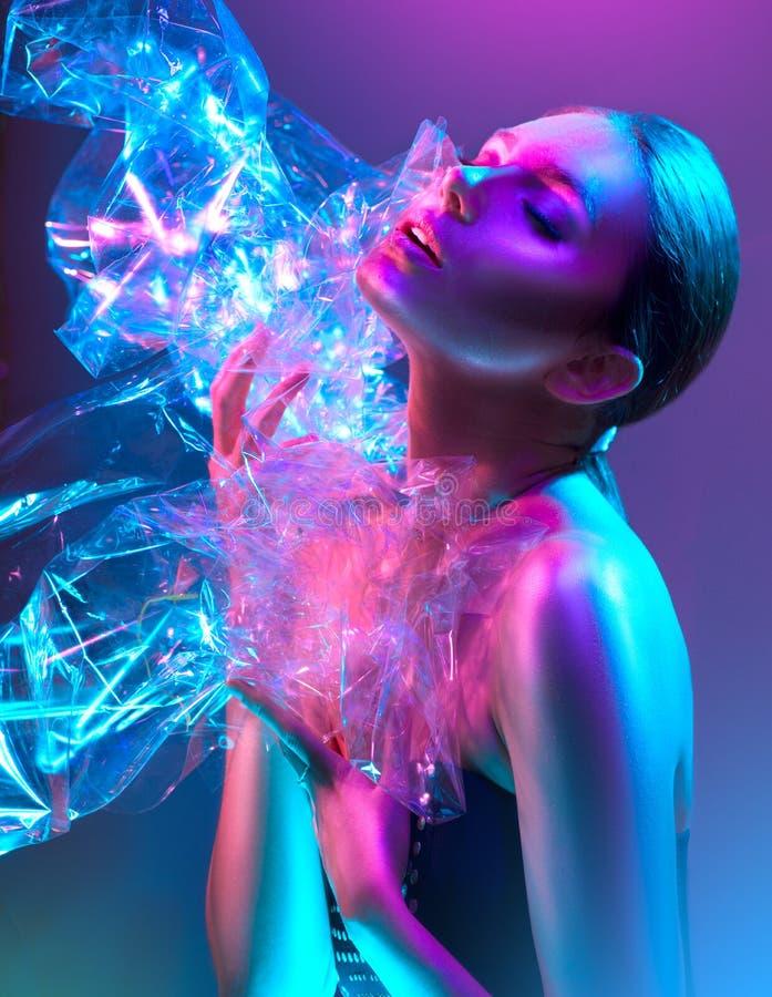 Femme de mannequin dans les lampes au néon lumineuses colorées posant dans le studio par le film transparent Portrait de belle fi photos libres de droits
