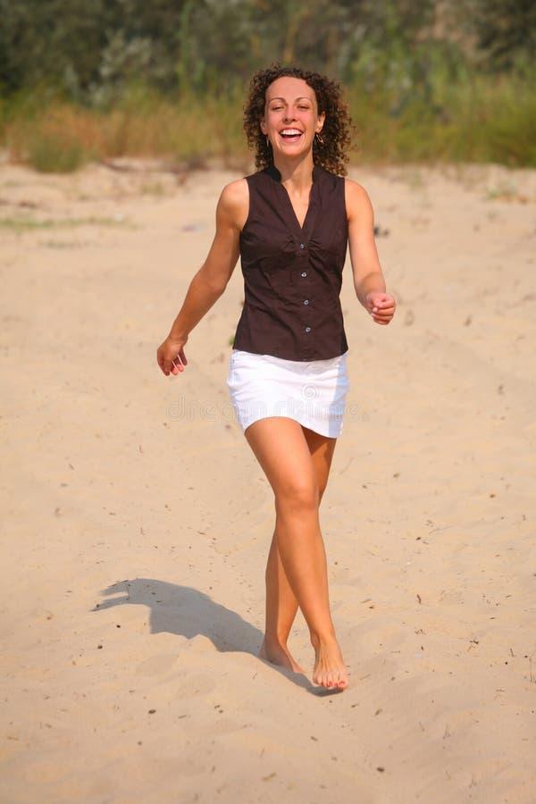 Femme de marche heureux sur le sable photo stock