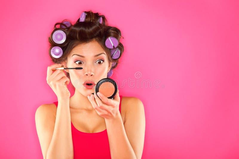 Femme de mascara de renivellement avec des rouleaux de cheveu image libre de droits