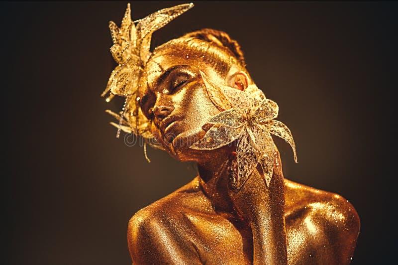 Femme de modèle d'or de mode avec les étincelles d'or lumineuses sur la peau posant, fleur d'imagination Portrait de belle fille  photo libre de droits