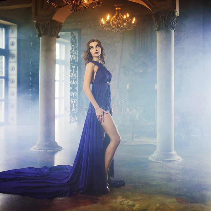 Femme de modèle de brune de beauté en égalisant la robe pourpre Maquillage de luxe et coiffure de belle mode images stock