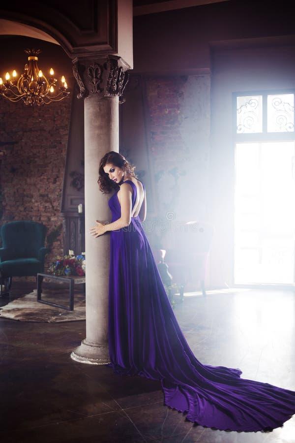 Femme de modèle de brune de beauté en égalisant la robe pourpre Maquillage de luxe et coiffure de belle mode photographie stock