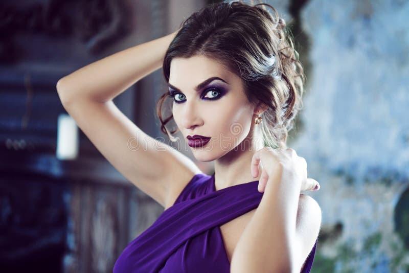 Femme de modèle de brune de beauté en égalisant la robe pourpre Maquillage de luxe et coiffure de belle mode images libres de droits