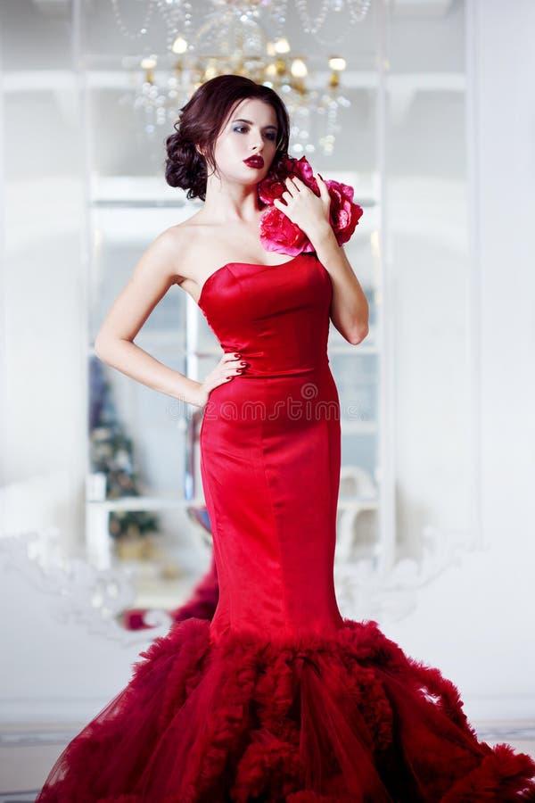 Femme de modèle de brune de beauté en égalisant la robe rouge image libre de droits