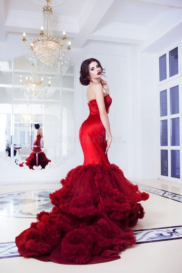 Femme de modèle de brune de beauté en égalisant la robe rouge photos libres de droits
