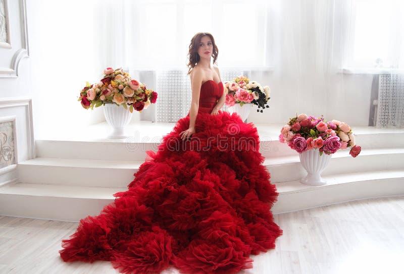 Femme de modèle de brune de beauté en égalisant la robe rouge Bel ennui photos libres de droits