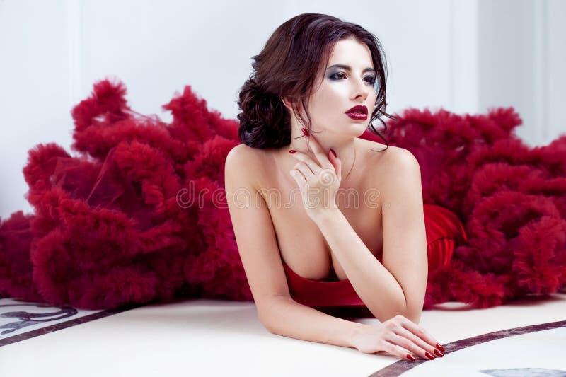 Femme de modèle de brune de beauté en égalisant la robe rouge Maquillage de luxe et coiffure de belle mode photographie stock