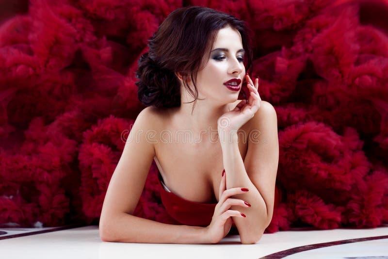 Femme de modèle de brune de beauté en égalisant la robe rouge Maquillage de luxe et coiffure de belle mode photos stock