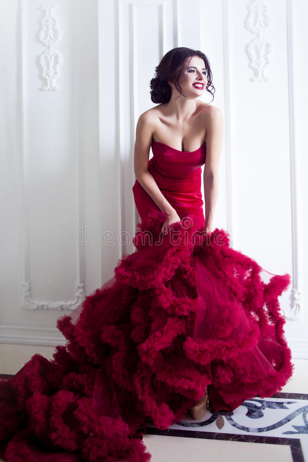 Femme de modèle de brune de beauté en égalisant la robe rouge Maquillage de luxe et coiffure de belle mode, intégraux photo stock