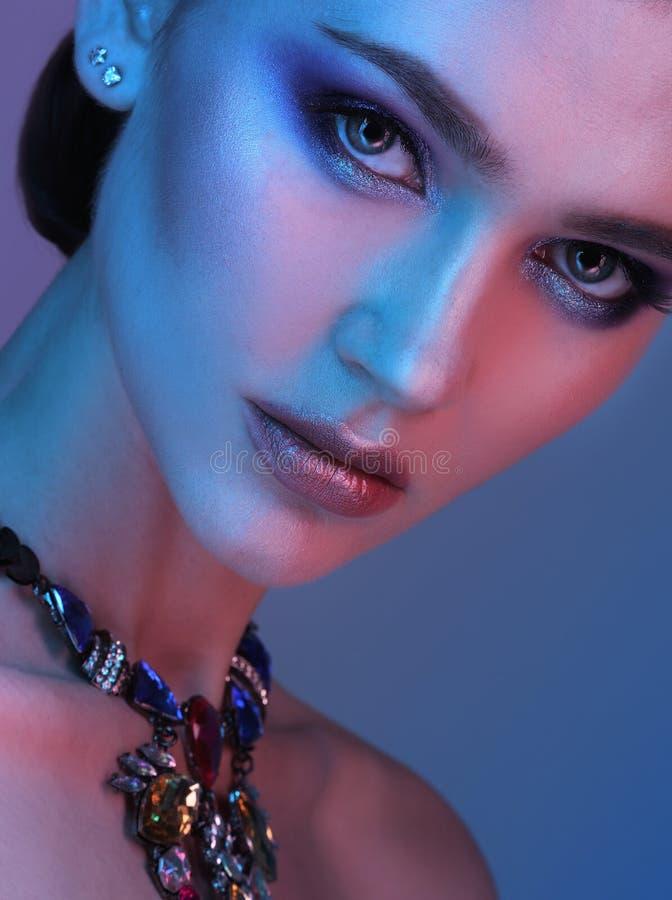 Femme de modèle de haute couture dans les lumières lumineuses colorées posant dans le studio photos stock