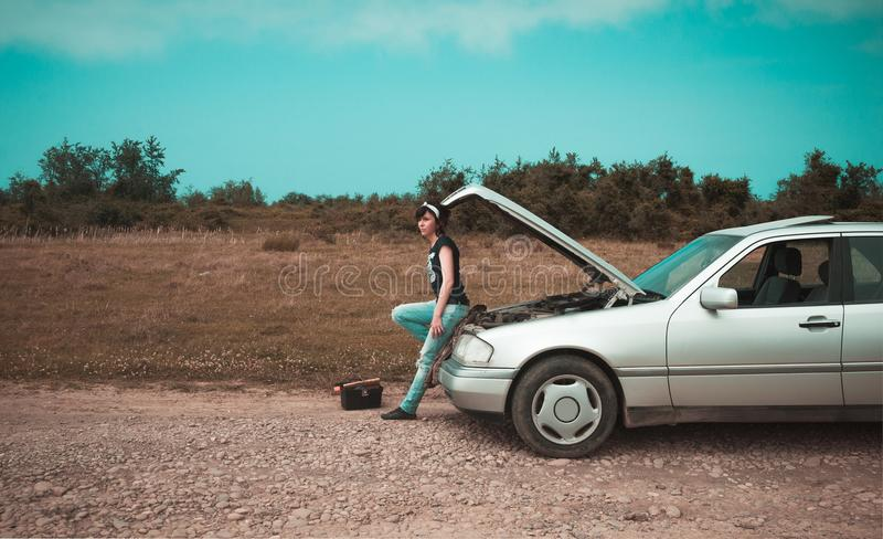 Femme de mode ayant des ennuis avec la voiture photographie stock libre de droits