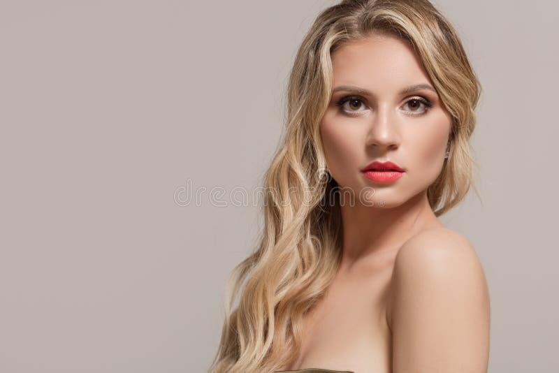 Femme de mode blonde avec de longs cheveux onduleux Femme avec le beau renivellement image stock