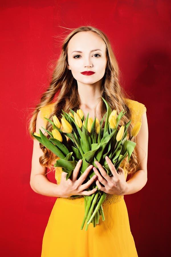 Femme de mode portant la robe jaune sur le rouge image stock