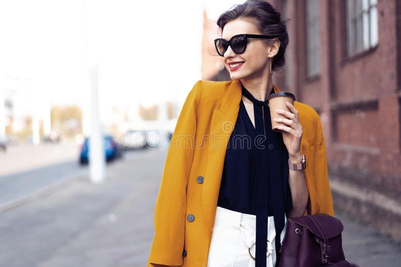 Femme de mode de portrait dans des lunettes de soleil marchant sur la rue Elle utilise la gu?pe, souriant pour d?grossir photo stock