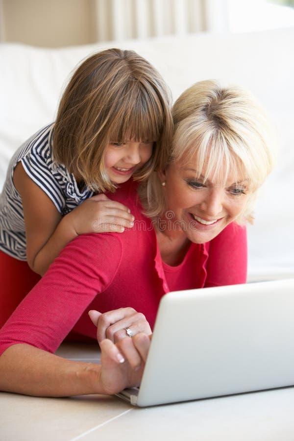 Femme de Moyen Âge avec la jeune fille à l'aide de l'ordinateur portatif photo libre de droits
