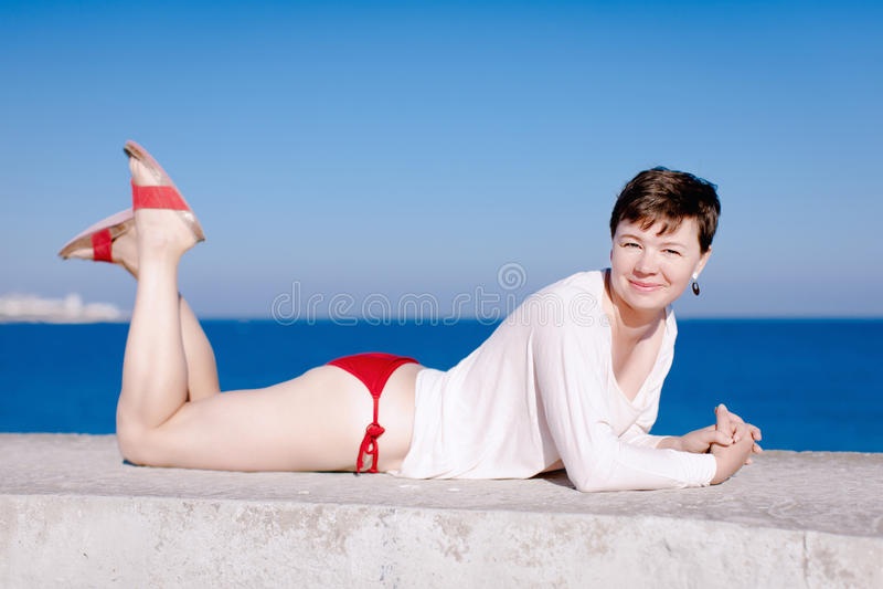 Femme de Moyen Âge dans le bikini rouge se trouvant sur l'avant images libres de droits