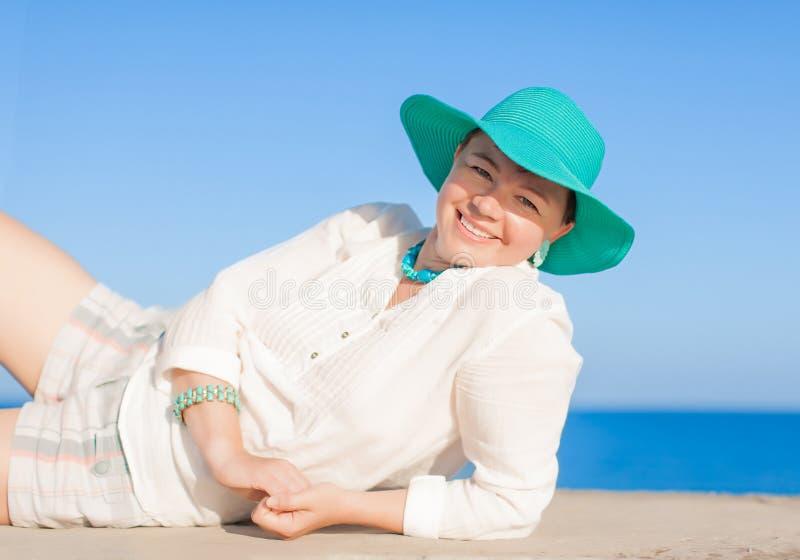 Femme de Moyen Âge dans le chapeau de turquoise se trouvant du côté photographie stock