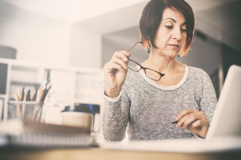Femme de Moyen Âge à l'aide de l'ordinateur image libre de droits