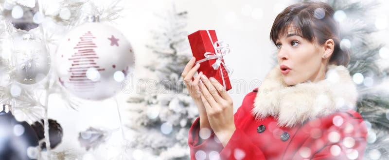 Femme de Noël étonnée avec le paquet de cadeaux sur la boule t de Noël photos stock