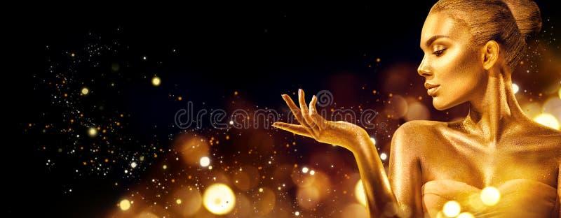 Femme de Noël d'or Fille de mannequin de beauté avec le maquillage d'or, les cheveux et les bijoux dirigeant la main sur le noir photos libres de droits