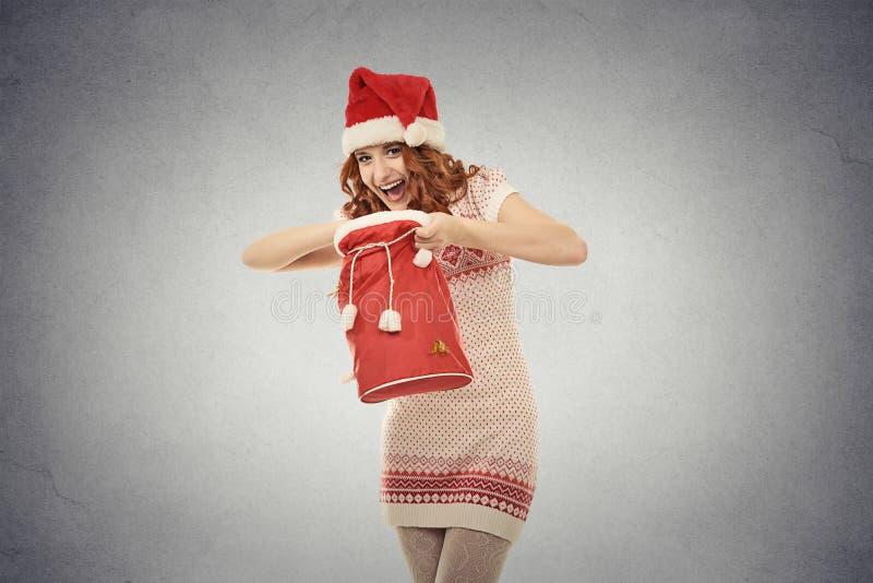 Femme de Noël dans le chapeau rouge du père noël tenant le sac de cadeau d'ouverture photos stock