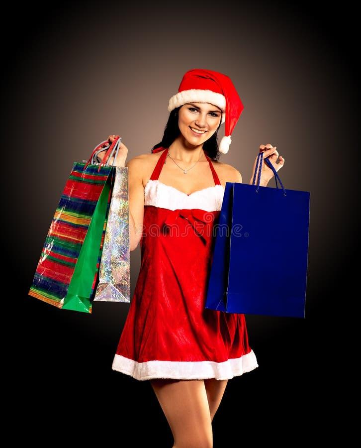 Femme de Noël de chapeau de Santa tenant des cadeaux de Noël image libre de droits