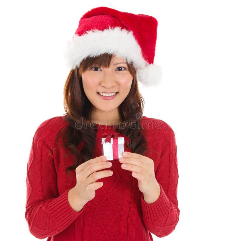Femme de Noël de chapeau de Santa tenant le cadeau de Noël photo libre de droits