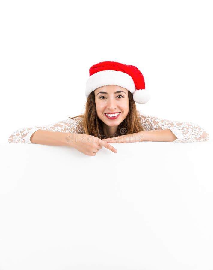 Femme de Noël indiquant l'espace de copie sur un panneau d'affichage vide photos stock