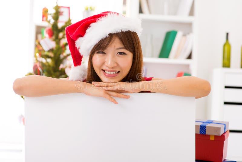 Femme de Noël se penchant au-dessus du signe de panneau-réclame photos stock