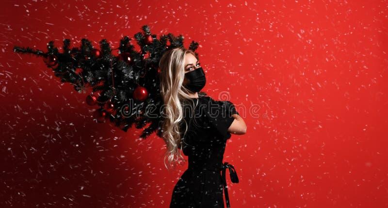 Femme de Noël utilisant les gants noirs de masque et la robe médicale tenant l'arbre de Noël sur ses épaules sous la neige sur le images libres de droits