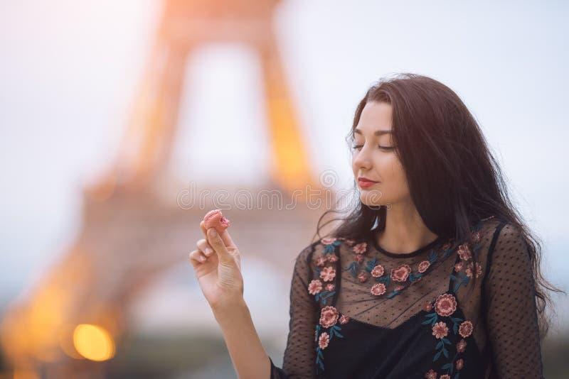 Femme de Paris souriant mangeant le macaron de pâtisserie française à Paris contre Tour Eiffel image libre de droits