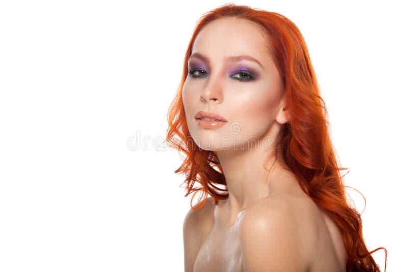 Femme de peau juste avec de longs cheveux rouges bouclés de beauté Fond d'isolement photo stock