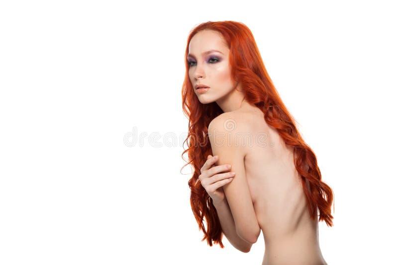 Femme de peau juste avec de longs cheveux rouges bouclés de beauté Fond d'isolement image stock