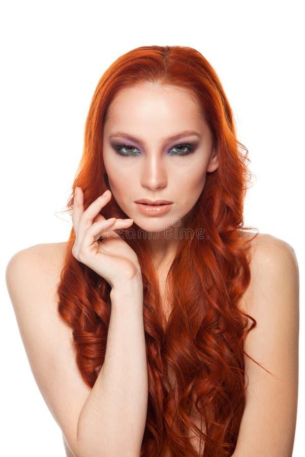 Femme de peau juste avec de longs cheveux rouges bouclés de beauté Fond d'isolement photographie stock