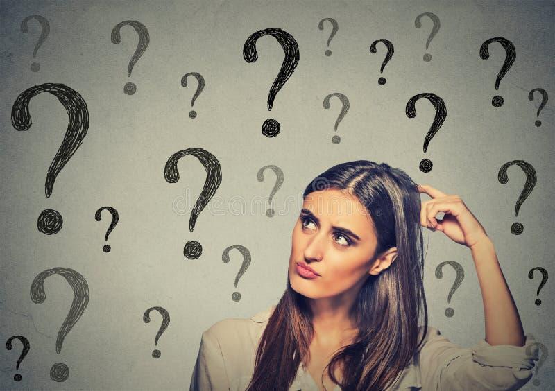 Femme de pensée confuse rayant sa tête regardant beaucoup de points d'interrogation image stock
