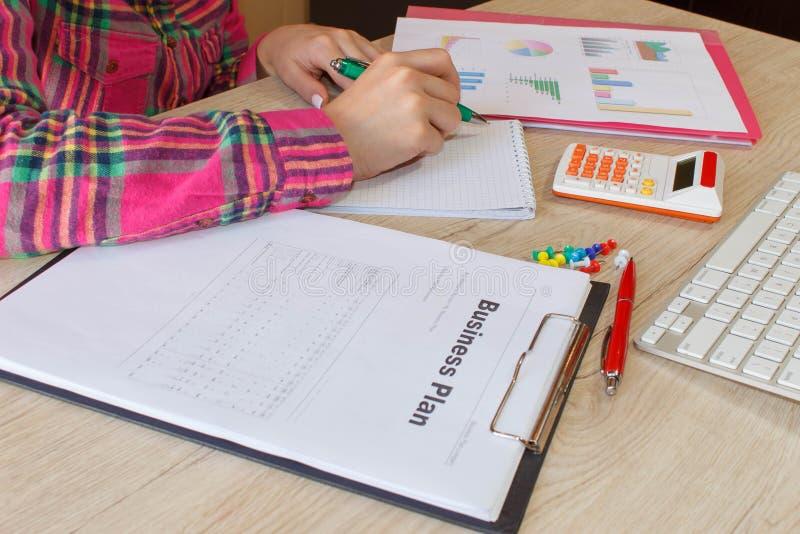Femme de personne dirigeant les buts d'écriture sur un papier, plan d'action d'écriture sur le lieu de travail, stylos de partici photographie stock libre de droits
