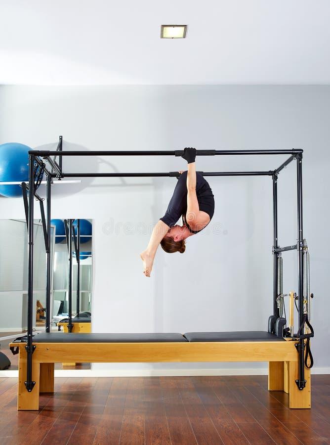 Femme de Pilates dans à l'envers acrobatique de Cadillac photo stock
