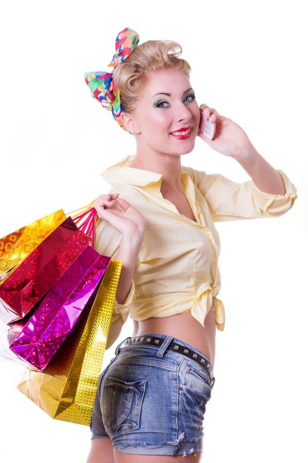 Femme de pin-up gaie avec les paniers et le téléphone photographie stock