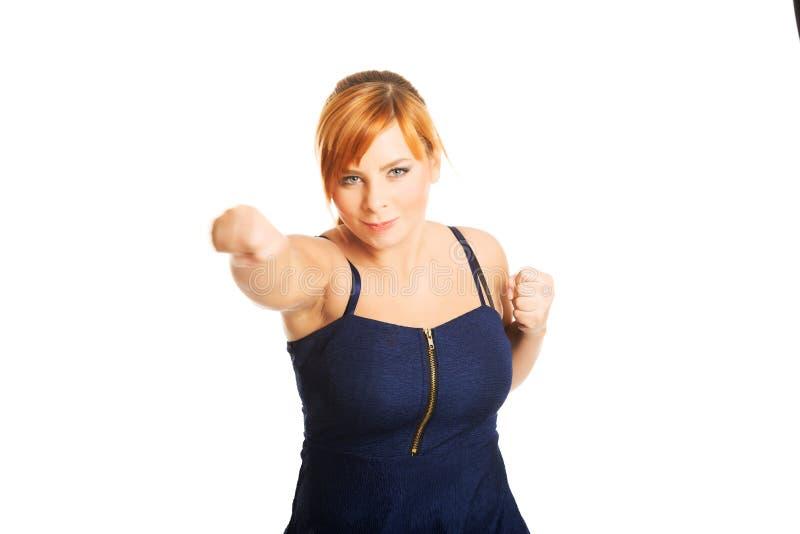Femme de poids excessif avec ses poings  image libre de droits