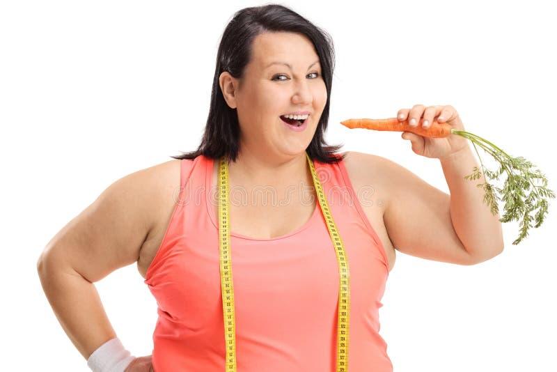 Femme de poids excessif avec une bande de mesure ayant une carotte photographie stock